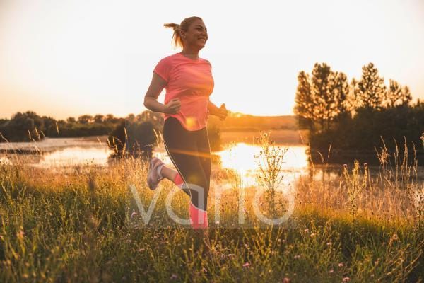 Smiling woman jogging on meadow during sunset