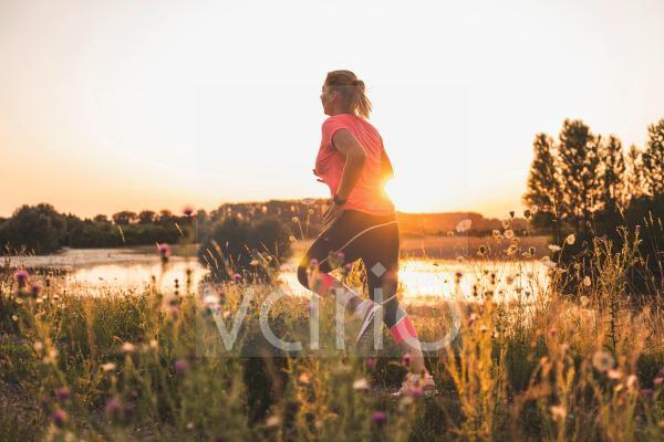 Mature woman running on meadow