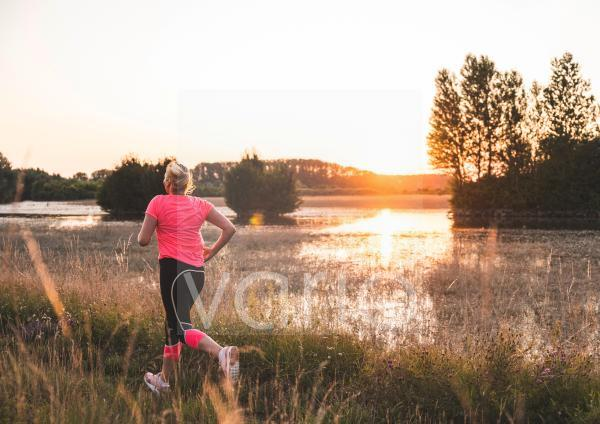 Woman exercising while running on grass during sunset