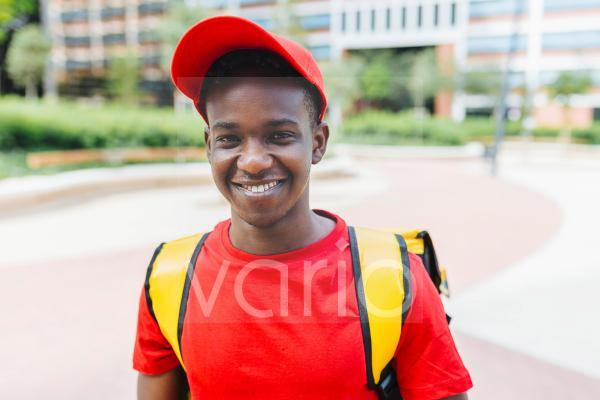 Smiling young delivery man wearing backpack