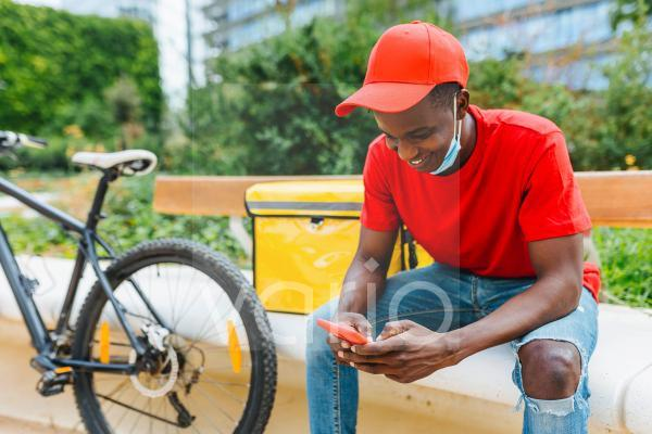 Smiling delivery man using mobile phone on bench during COVID-19