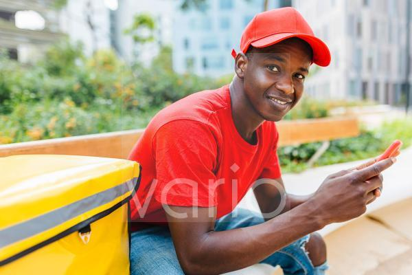 Smiling young delivery man holding smart phone while sitting on bench