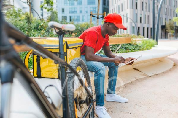 Young delivery man using digital tablet while sitting by package on bench