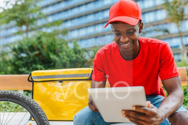 Smiling delivery man using digital tablet on bench