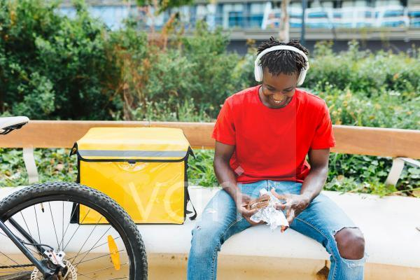 Happy delivery man listening music through wireless headphones while eating food on bench