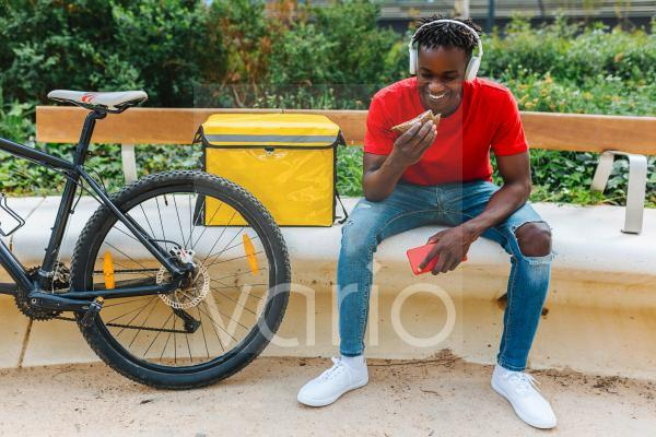 Smiling young delivery man eating food while sitting by bicycle on bench