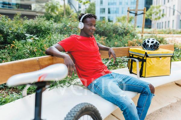 Delivery man listening music through headphones while sitting on bench