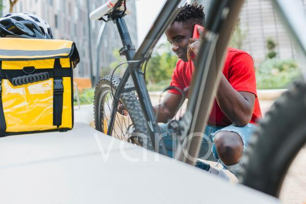 Delivery man talking on smart phone while checking bicycle