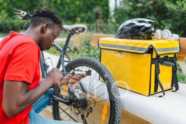 Young delivery man inflating bicycle by bench