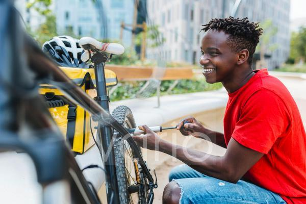 Happy young delivery man inflating bicycle