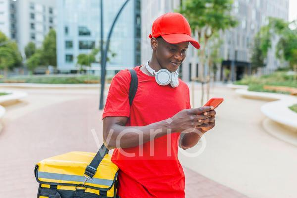 Delivery man wearing backpack text messaging through mobile phone