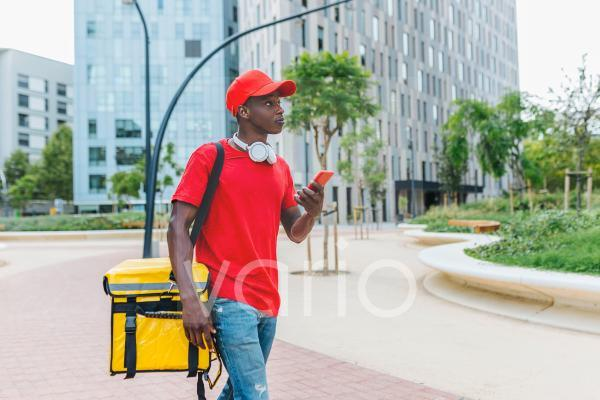 Delivery man holding mobile phone while walking with backpack on footpath