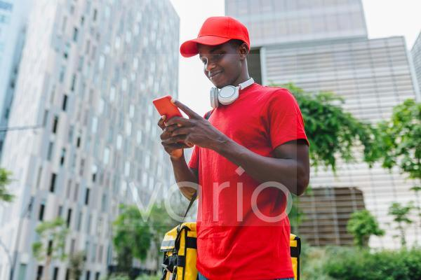 Smiling delivery man text messaging through smart phone in city