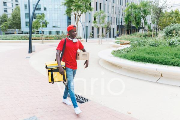 Young delivery person with backpack and package walking on footpath in city