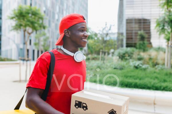 Happy young delivery man carrying box