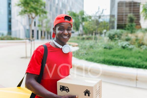 Smiling young delivery man carrying package
