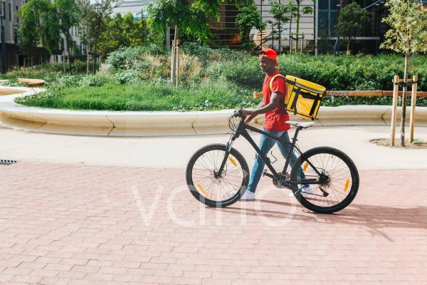 Delivery man with bicycle walking on footpath during sunny day