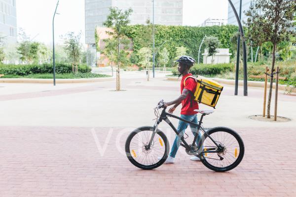 Delivery man wearing helmet while wheeling bicycle on footpath