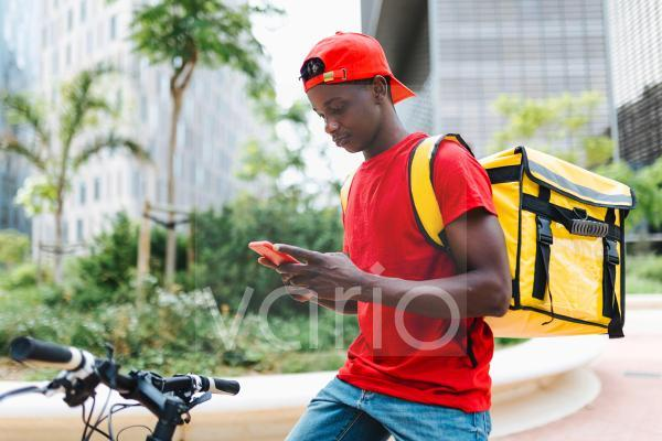 Young delivery man using smart phone while sitting on bicycle