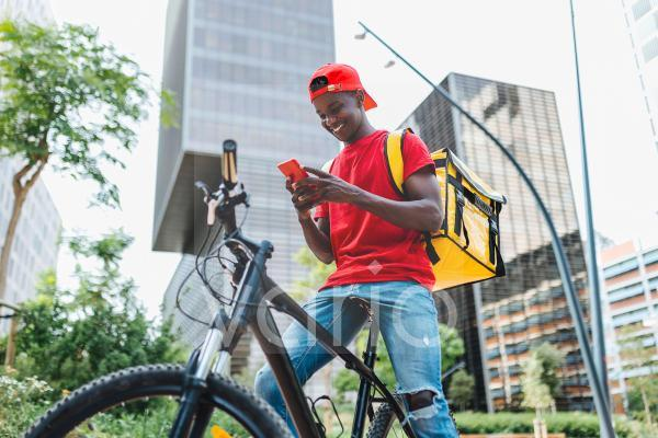 Smiling delivery man using mobile phone while sitting on bicycle in city