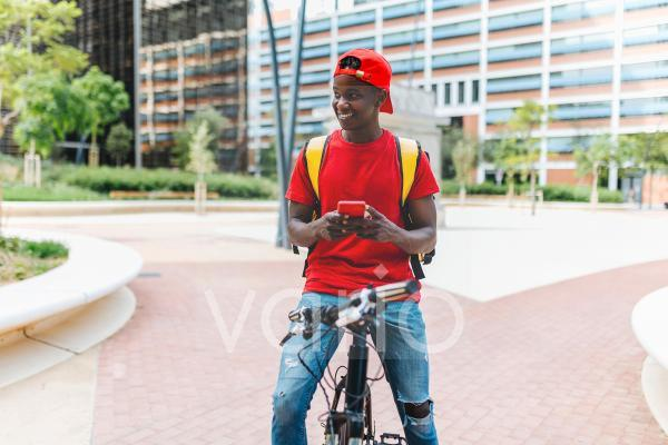 Smiling delivery man holding mobile phone while sitting on bicycle in city