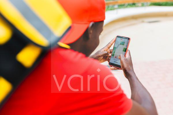 Young delivery man using map while working
