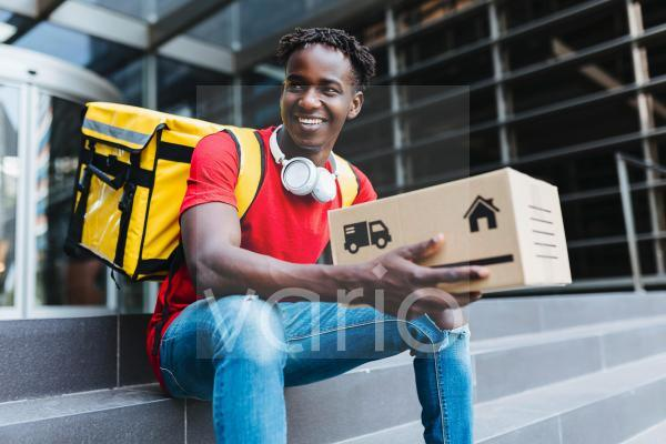 Happy delivery man holding box while sitting on steps