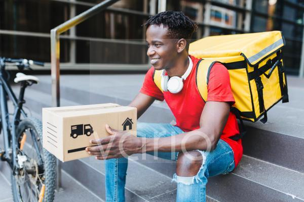 Smiling delivery man with package sitting on steps