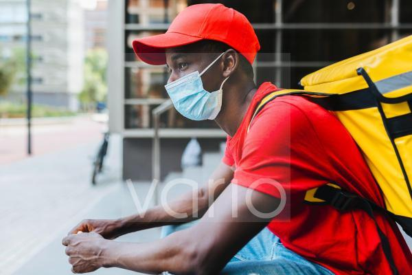 Young delivery man wearing protective face mask during COVID-19