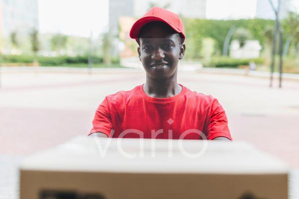 Smiling young delivery man wearing cap delivering package