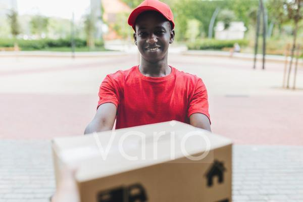 Smiling delivery man giving package to customer