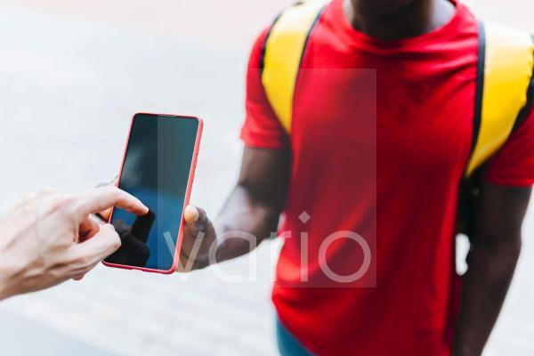 Male customer signing on mobile phone while receiving package