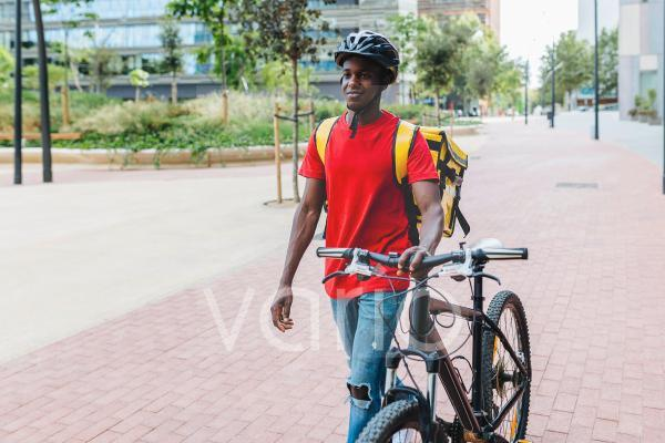 Smiling delivery man with bicycle walking on footpath