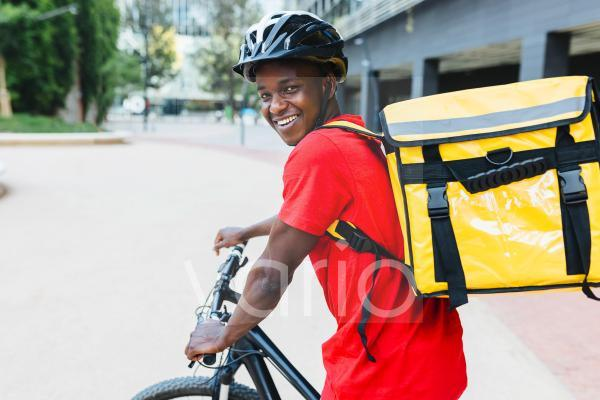 Happy young delivery man wearing backpack sitting on bicycle
