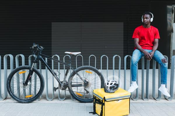 Delivery man listening music while sitting on railing
