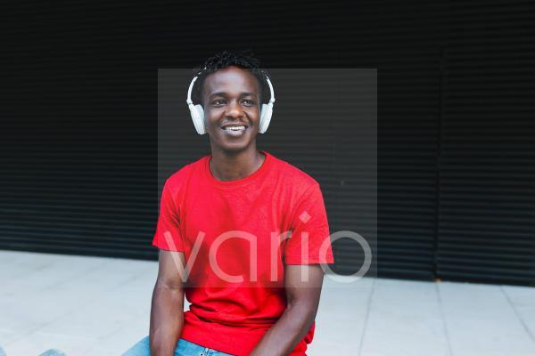 Smiling young man listening music in front of black wall