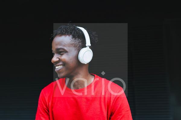 Happy young man listening music through headphones in front of black wall