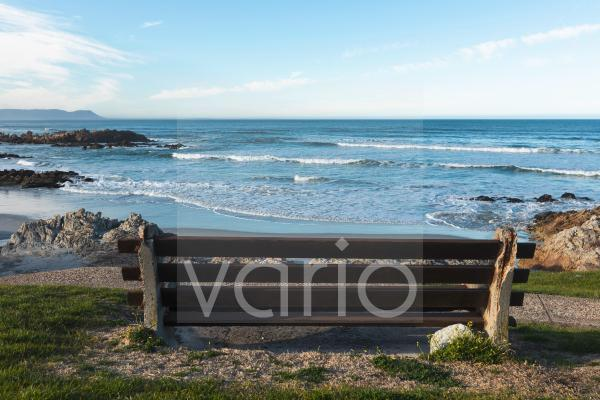Bench overlooking a beach, jagged rocks and rockpools on the Atlantic coast.