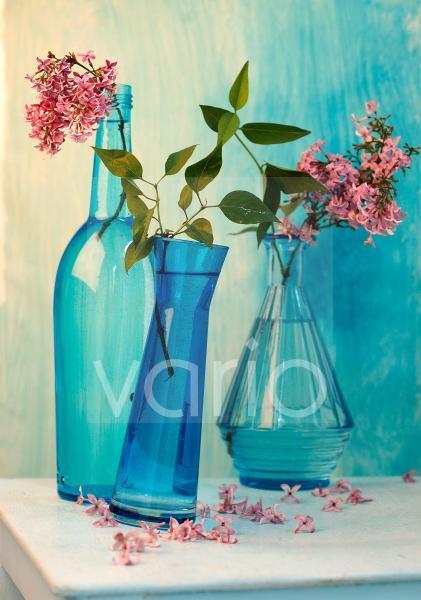 Fliederblüten in blauen Flaschen