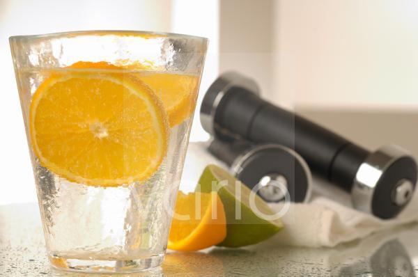 Mineralwasser mit Zitronenscheibe und Hanteln