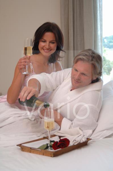 Paar im Bett mit Sekt