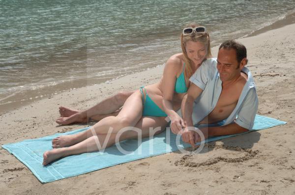 Paar liegt am Strand; Mann malt ein Herz in den Sand