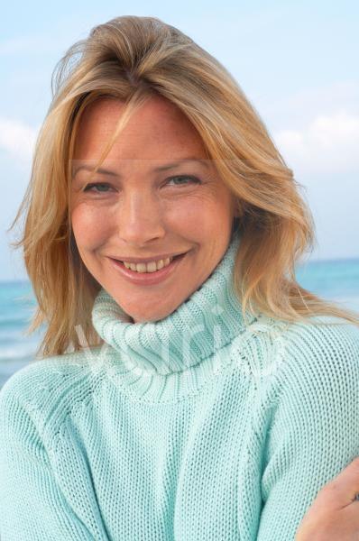Frau im türkisen Pullover am Meer