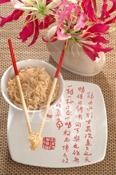 Asiatische Nudelschale mit Essstäbchen und Blume