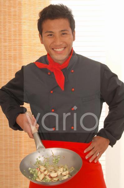 Asiatischer Koch mit Wokpfanne