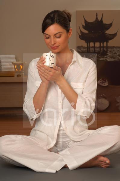Frau im Yogasitz mit Teetasse