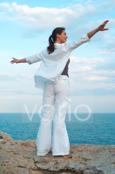 Frau auf einem Felsen am Meer