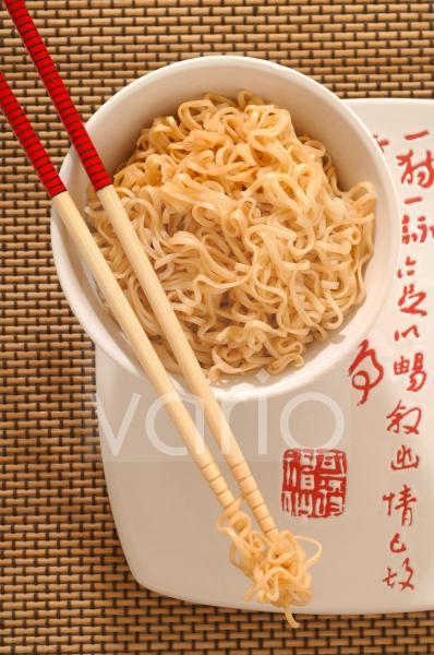 Asiatisches Nudelgericht in einer Schale mit Essstäbchen