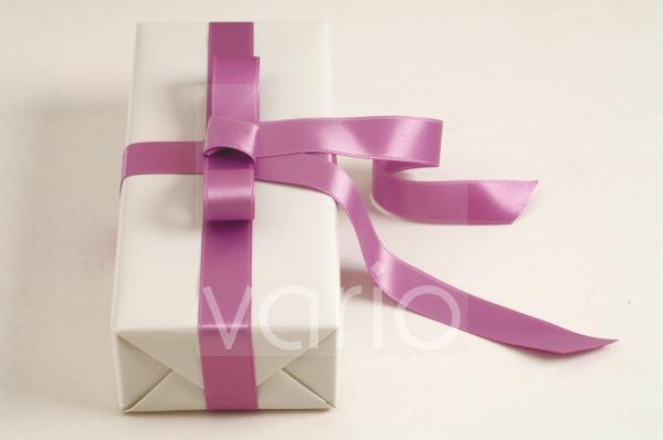 Weiß verpacktes Geschenk mit hell violetter Schleife