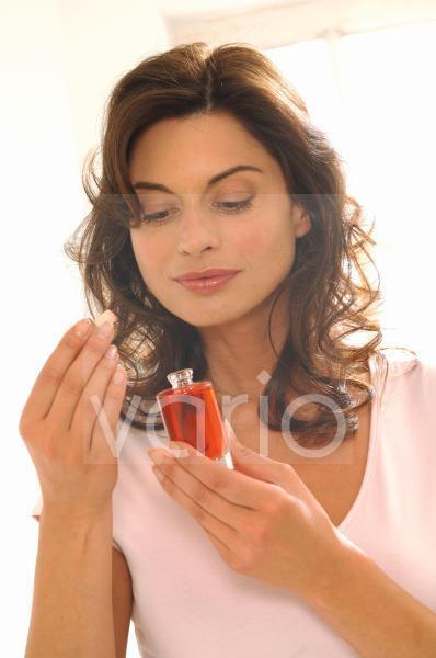 Frau riecht am Parfüm Flakon